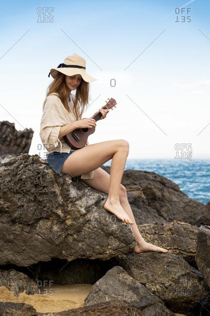 Smiling young woman wearing summer hat sitting on rock playing ukulele