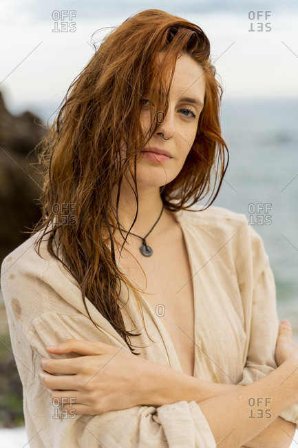 Portrait of redheaded young woman with nose piercing in front of the sea