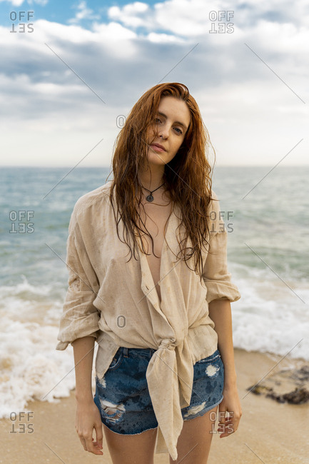 Portrait of redheaded young woman with nose piercing standing on the beach