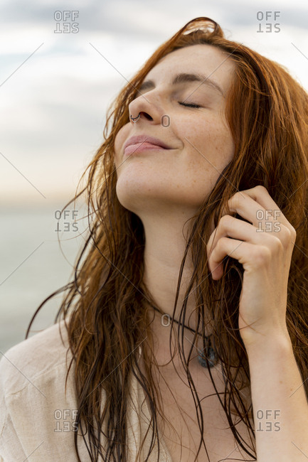 Portrait of happy redheaded young woman with nose piercing in front of the sea by sunset