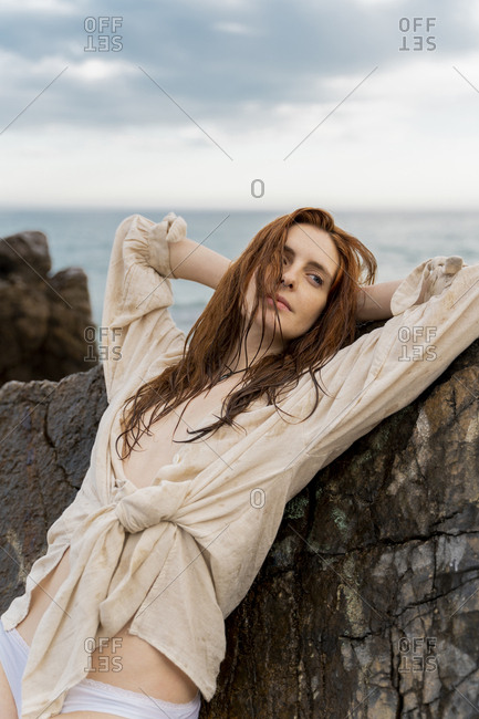 Portrait of redheaded young woman with nose piercing leaning against rock