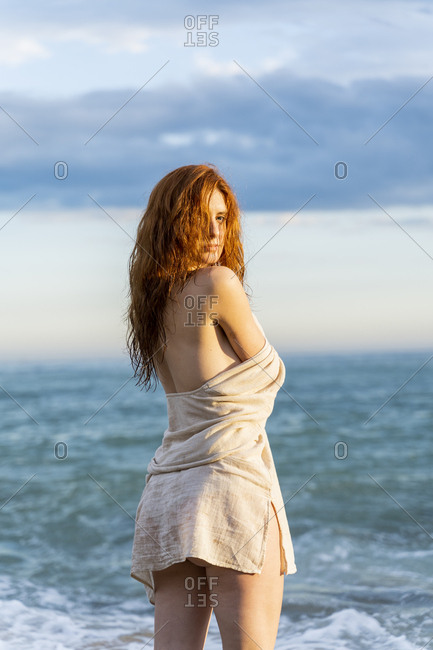 Portrait of redheaded young woman standing in front of the sea