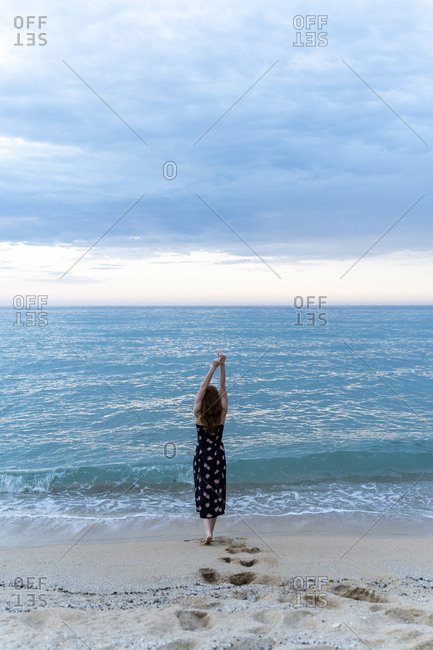 Back view of young woman at seafront