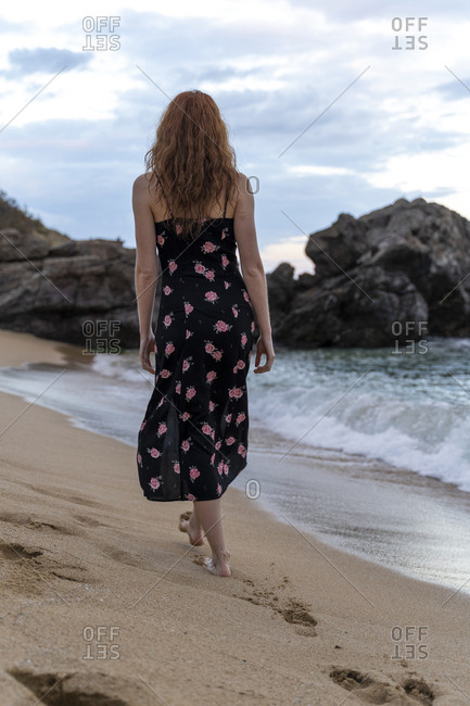 Back view of young woman wearing summer dress with floral design walking on the beach