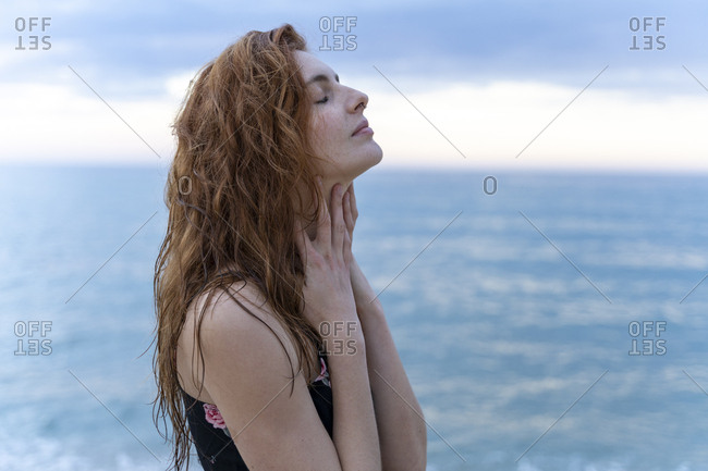 Young man with eyes closed in front of the sea