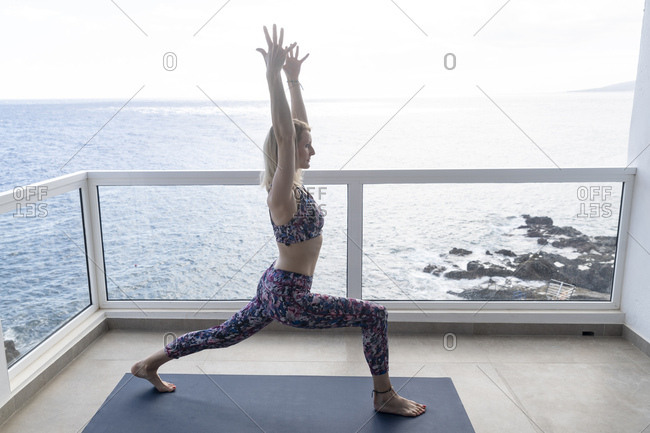 Woman practicing yoga on balcony- Position 'High Lunge'- Tenerife- Spain