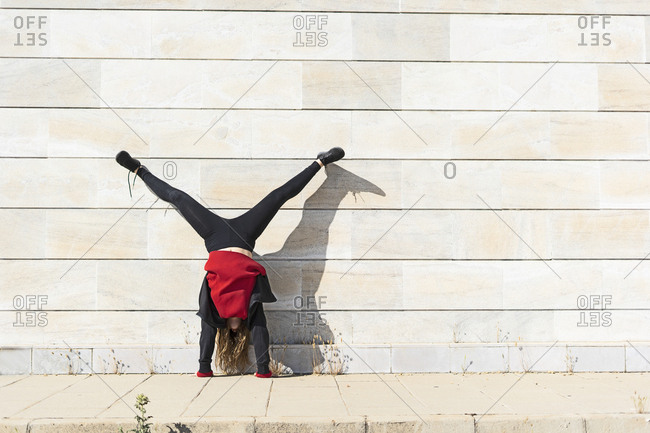 Teenage girl doing a handstand at a wall outdoors