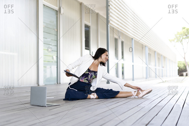 Female balett dancer sitting on the ground- using tablet and laptop