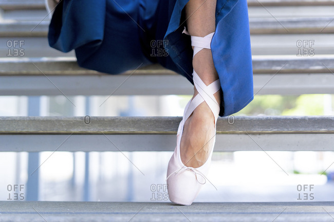 Female dancer with toe shoe sitting on steps