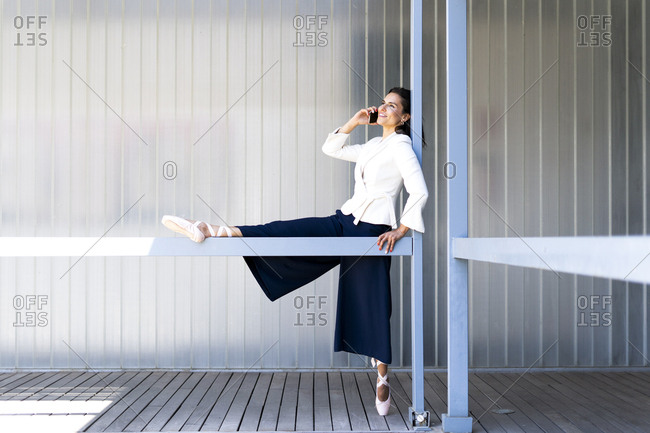 Female ballet dancer during training on a railing- using smartphone