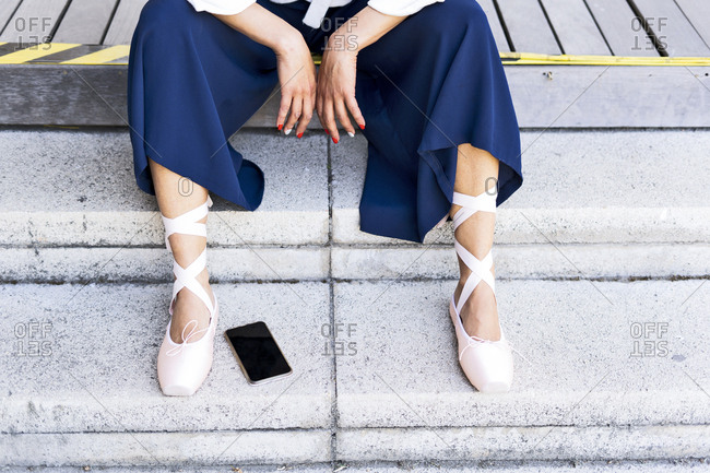 Female dancer with toe shoes sitting on steps