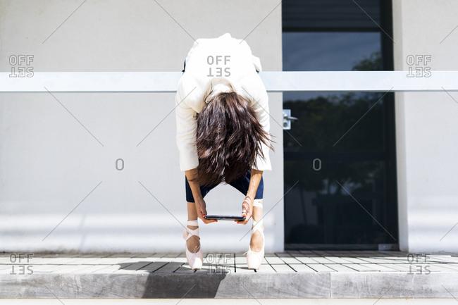 Female ballet dancer hanging over railing- holding tablet