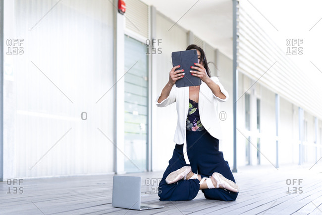 Female balett dancer kneeling on the ground- using tablet