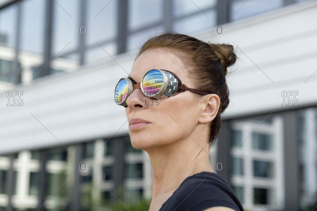 Mature woman wearing welder's goggles in front of an office building