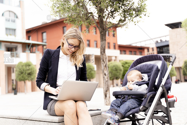 Young businesswoman with baby boy in stroller working on laptop outdoors