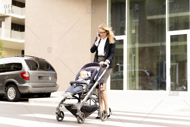 Smiling young businesswoman on the phone crossing street with baby boy in stroller