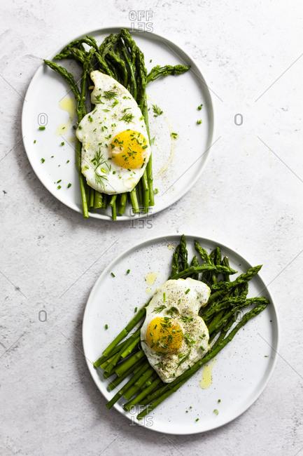 Asparagus and fried eggs on plates