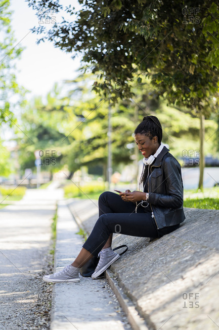 Smiling woman resting in urban park using cell phone
