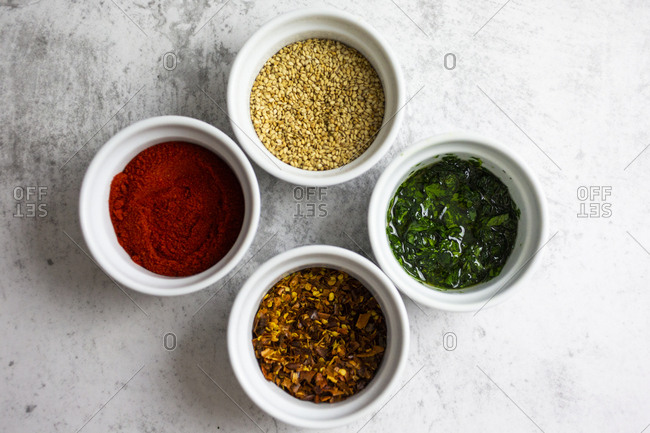 Paprika powder- chili flakes- sesame and parsley with oil in bowls