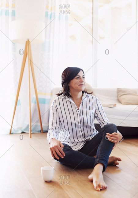 Mature woman sitting on floor at home- relaxing with a cup of coffee