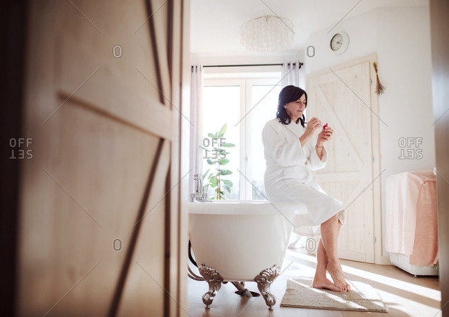 Mature woman sitting on bath tub- applying mascara