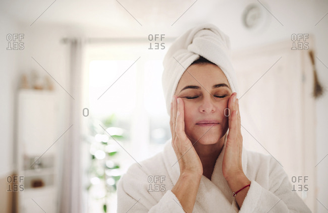 Portrait of mature woman in a bathroom at home applying moisturizer