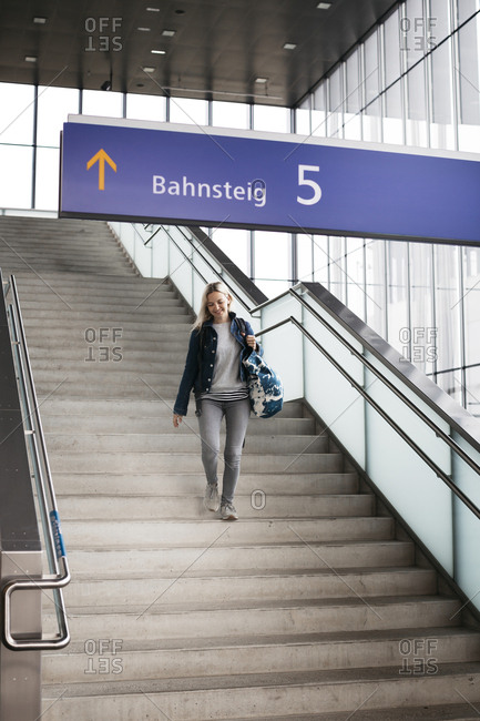 Smiling woman walking down stairs at the station