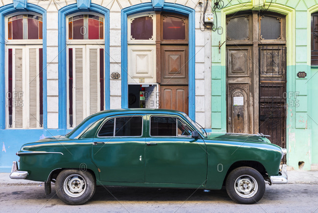 March 17, 2018: Green vintage car parked in front of house entrances- Havana- Cuba
