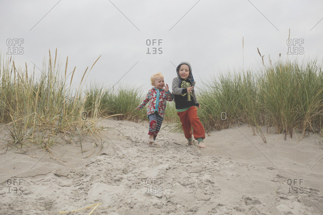 Boy and girl running to the beach together