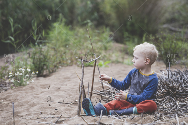 Little boy playing with sticks on the sand