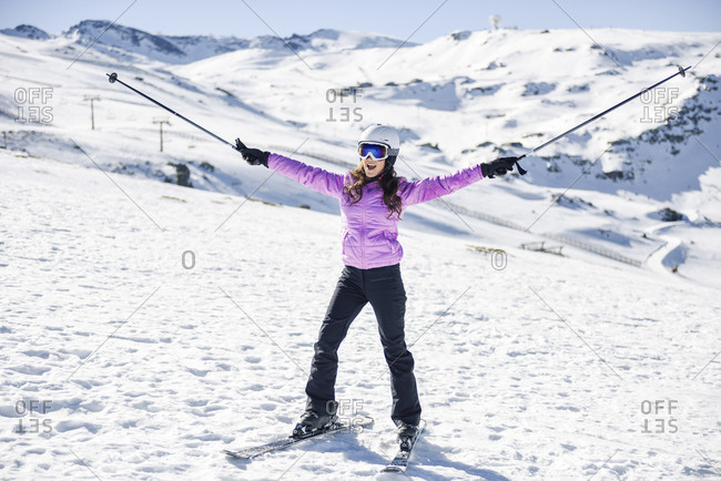 Happy woman raising her ski poles in snow-covered landscape in Sierra Nevada- Andalusia- Spain