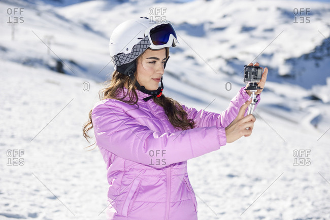 Woman in ski clothes filming with an action camera in snow covered-landscape