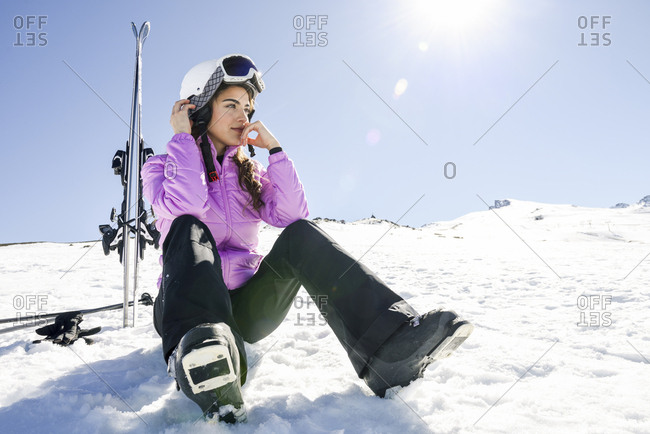 Woman taking a break after skiing sitting on the snowy ground in Sierra Nevada- Andalusia- Spain