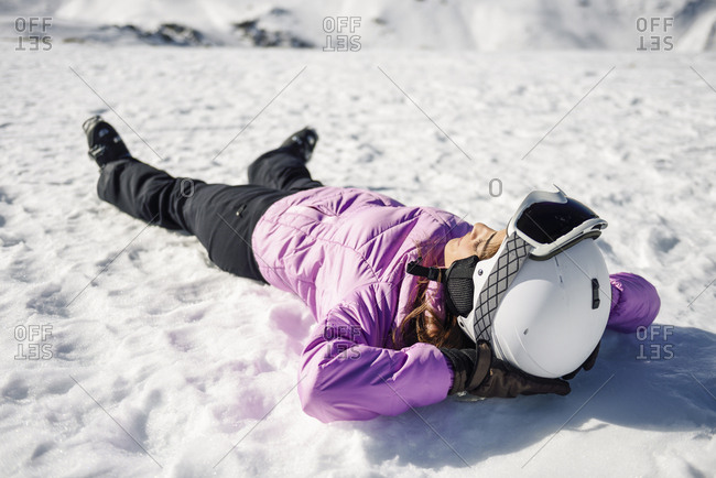 Woman taking a break after skiing lying on the snowy ground in Sierra Nevada- Andalusia- Spain
