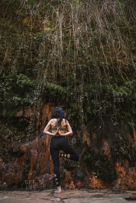Rear view of woman practicing yoga in nature