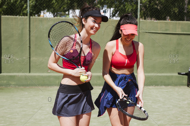 Two happy female tennis players on the court