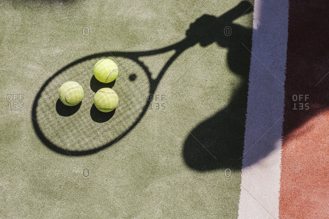 Shadow of a tennis player with balls and racket on court