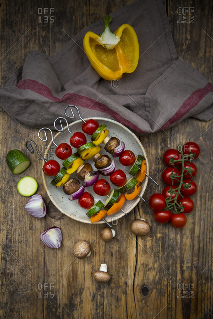 Grilled vegetable skewers on a plate and single ingredients