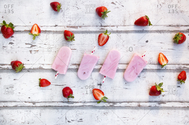 Homemade strawberry yogurt ice lollies with fresh strawberries on white wood