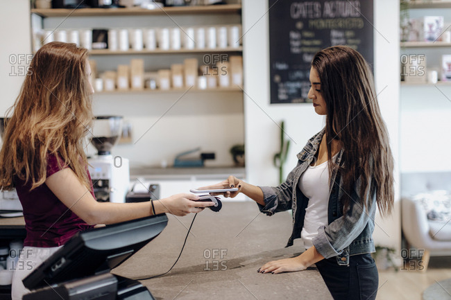 Young woman paying cashless with smartphone at the counter of a cafe