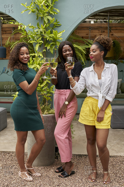 Three friends toasting with white wine having fun