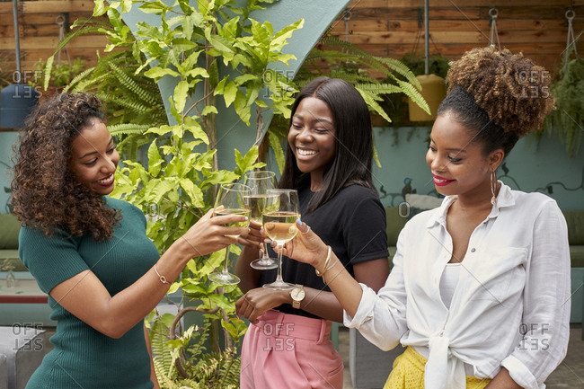 Three happy friends toasting with white wine