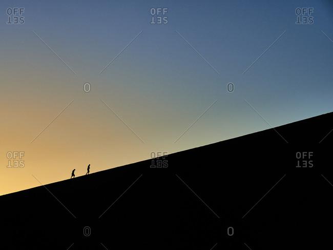 Silhouette of two people hiking on Big Daddy at sunrise- Namib desert- Namibia