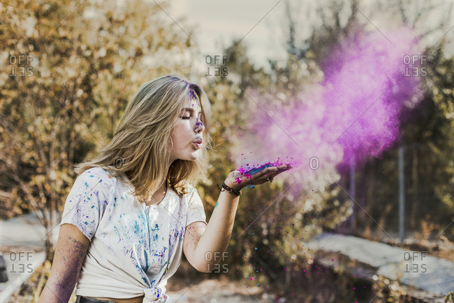Girl blowing Holi powder colors- Germany