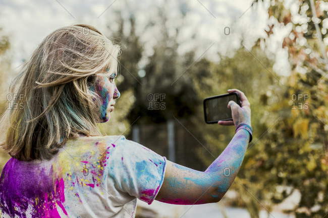Girl Holi powder colors in her face- taking selfie- Germany