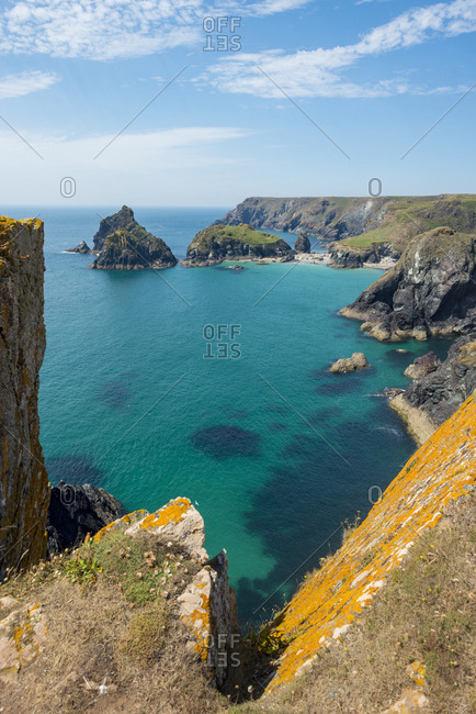 A distant view of Kynance Cove on the Lizard Peninsula in Cornwall on a sunny day