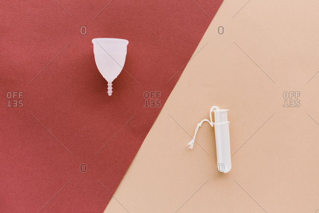 Menstrual cup and a tampon on a red and peach background