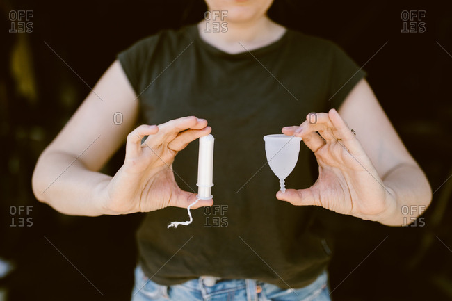 Woman holding a tampon and a silicone menstrual cup