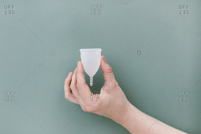 Hand holding a menstrual cup with blue background