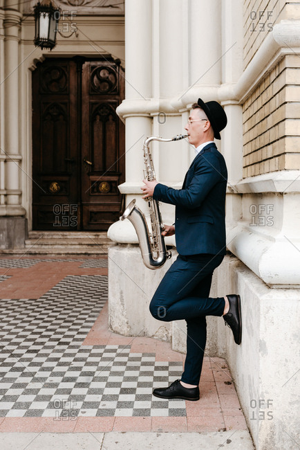 Young man in suit playing saxophone on the street
